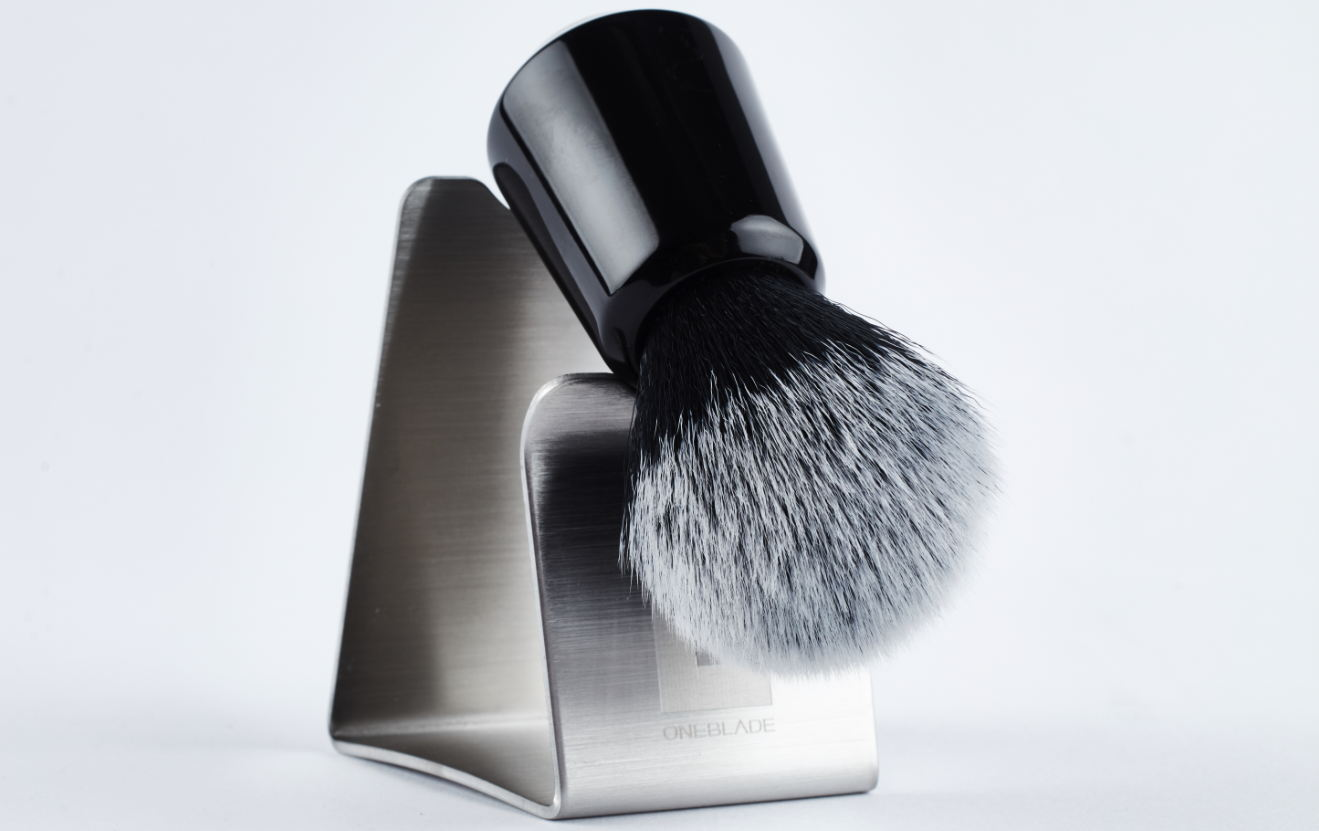 A shave brush perched on a shave brush stand with a white background