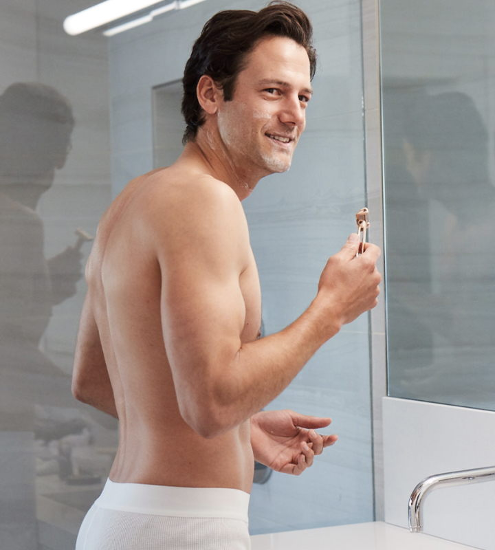 Man in bathroom holding OneBlade razor