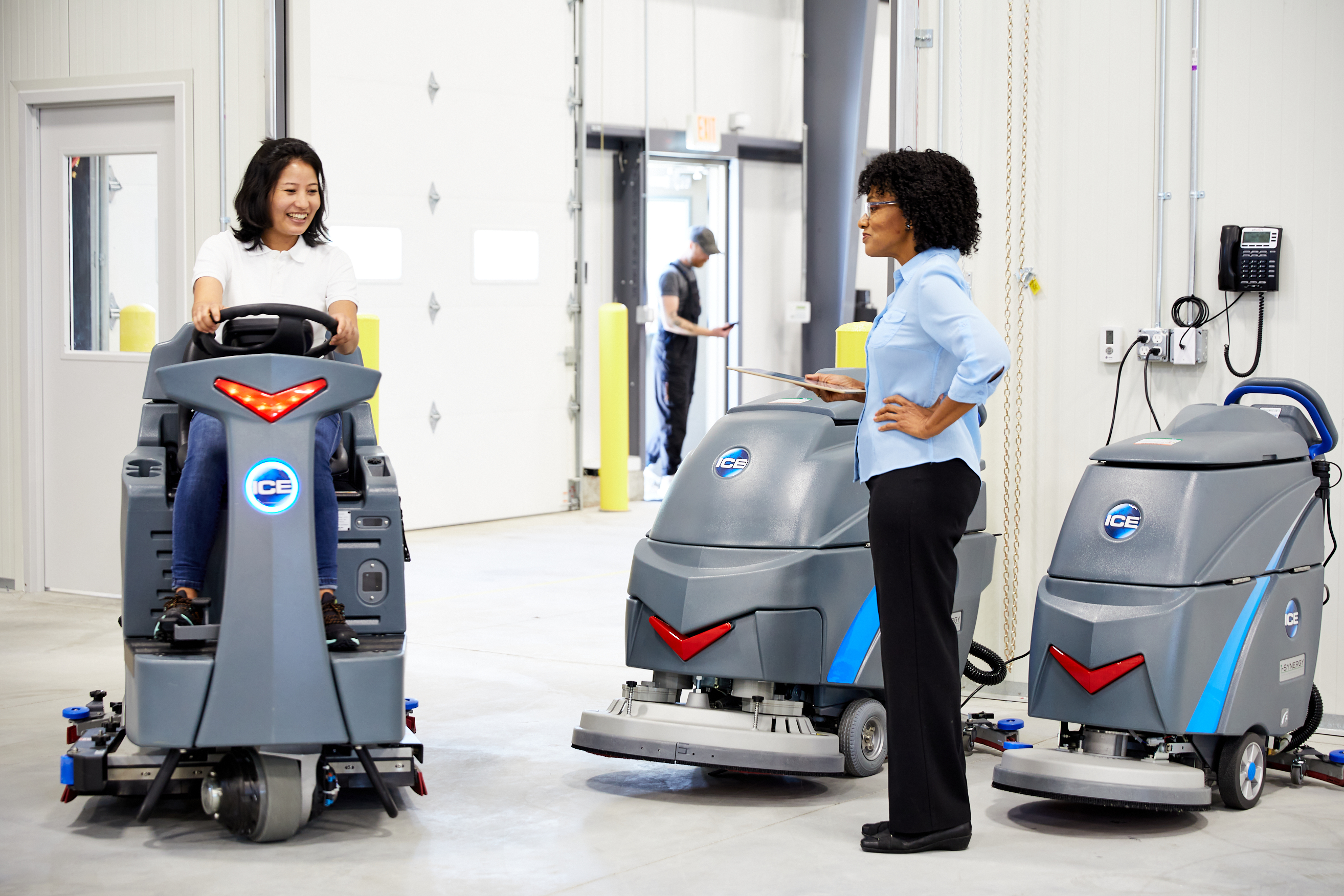 Women on a ride-on floor scrubber entering a warehouse with a lady standing next to multiple floor scrubbers