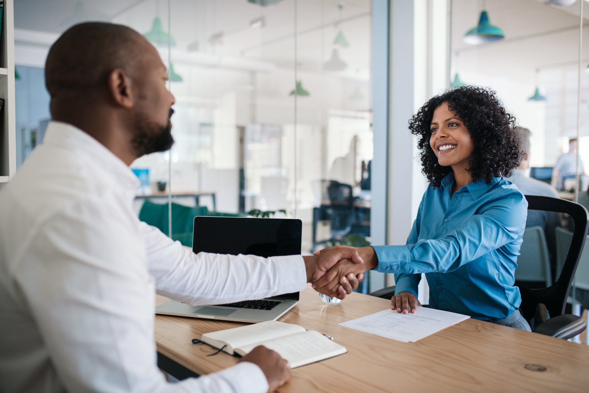 2 coworkers shaking hands over a desk in an office