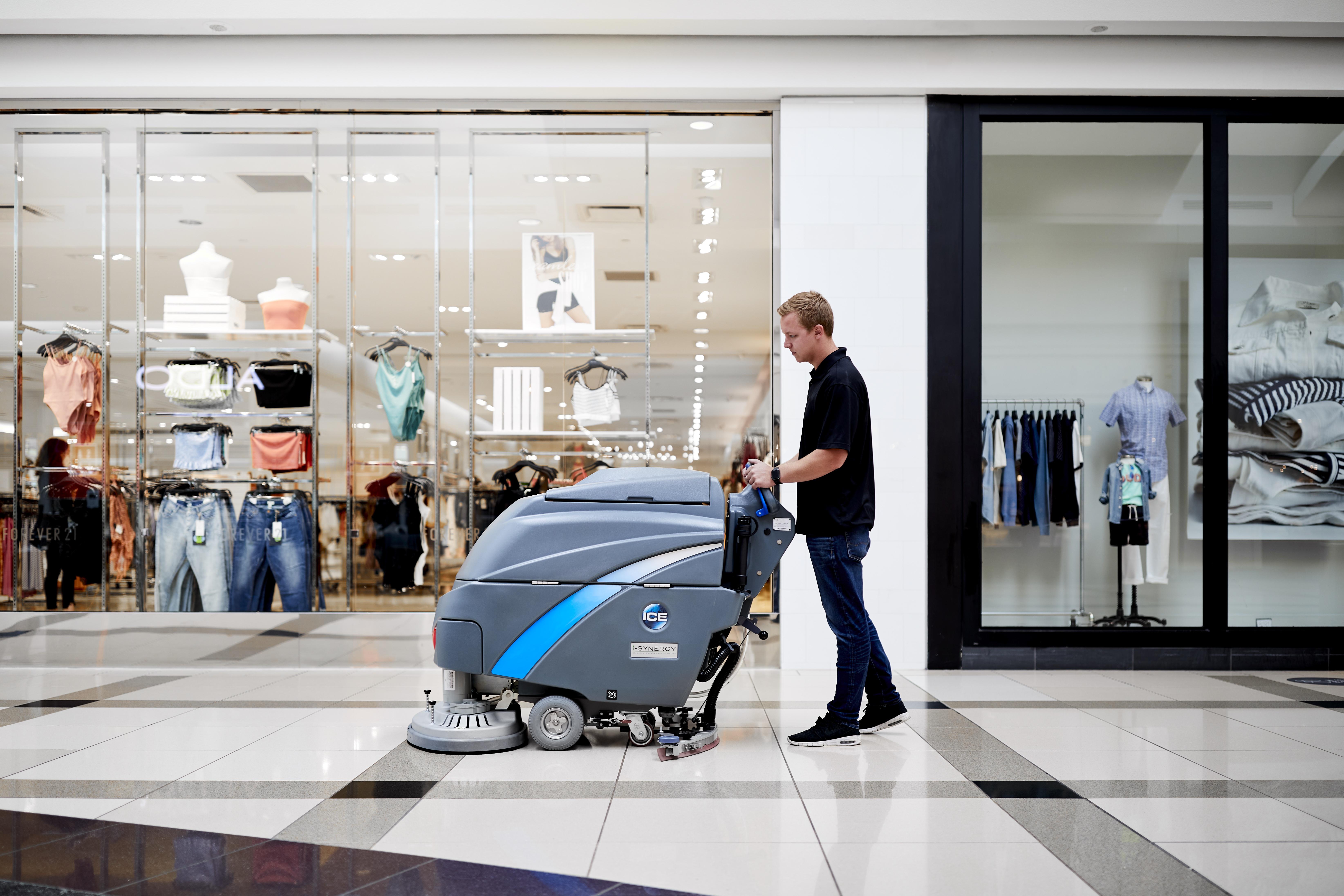 Machine operator pushing the i20btl scrubber through retail mall