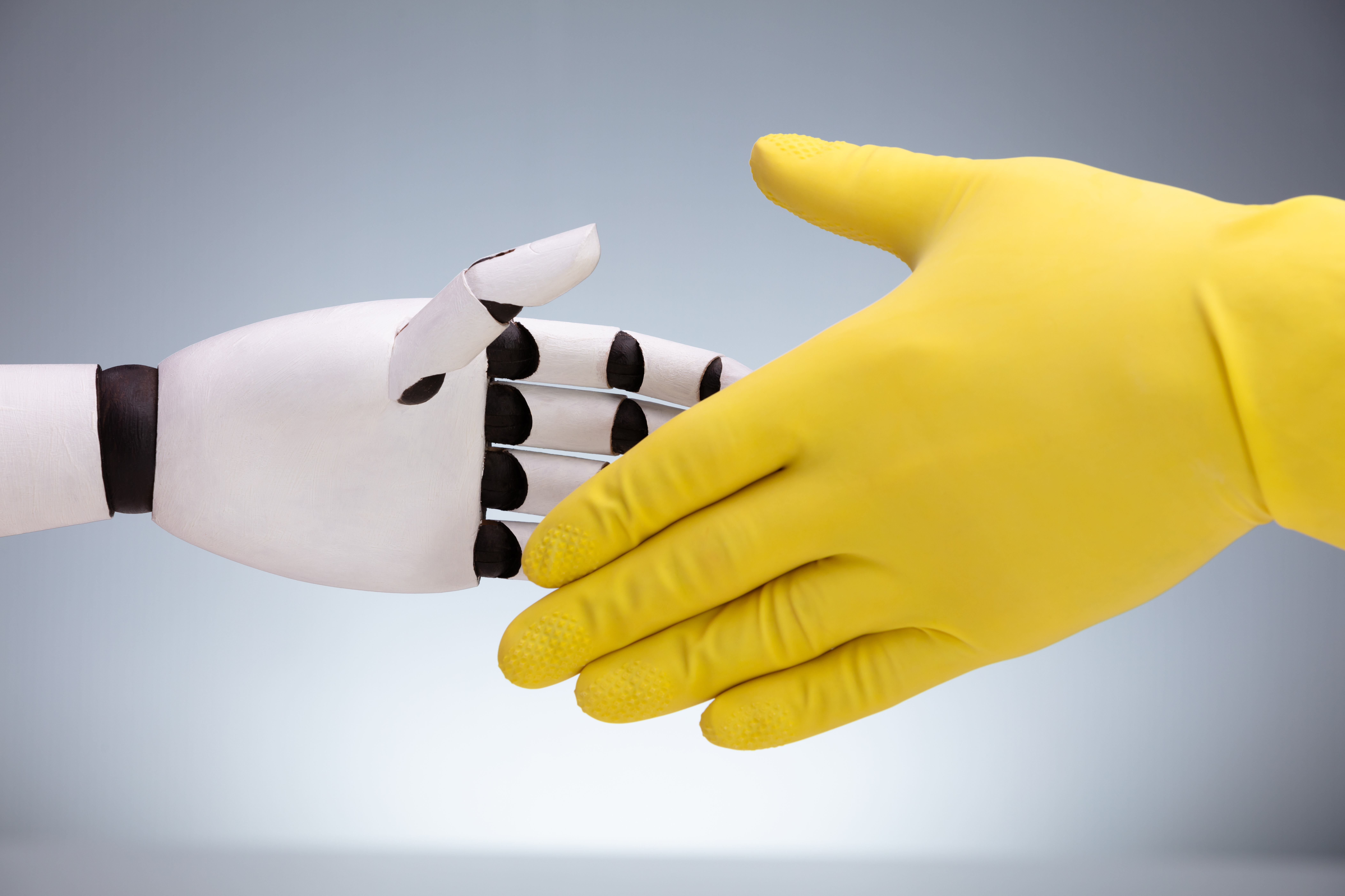 yellow rubber gloved hand shaking a robot hand