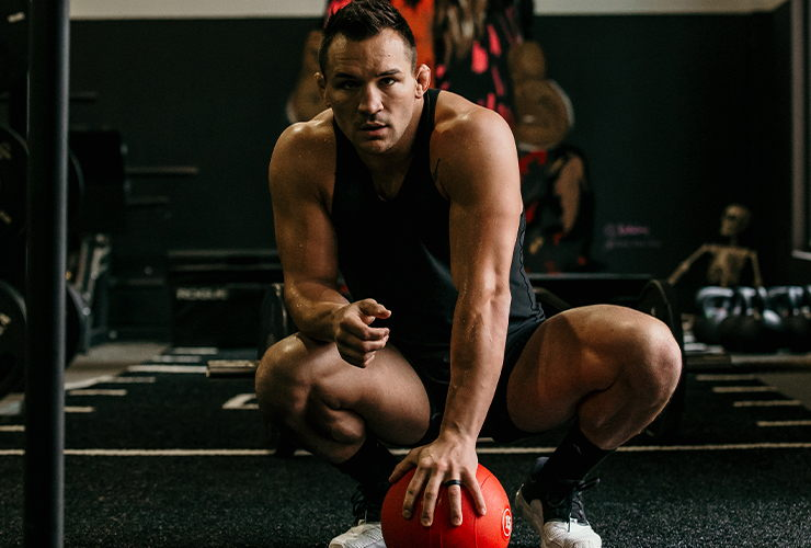 Michael Chandler crouches in a gym