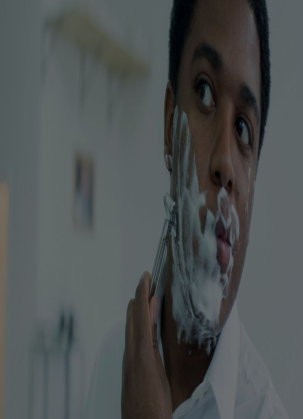 A man with shaving cream on his face looking into the mirror