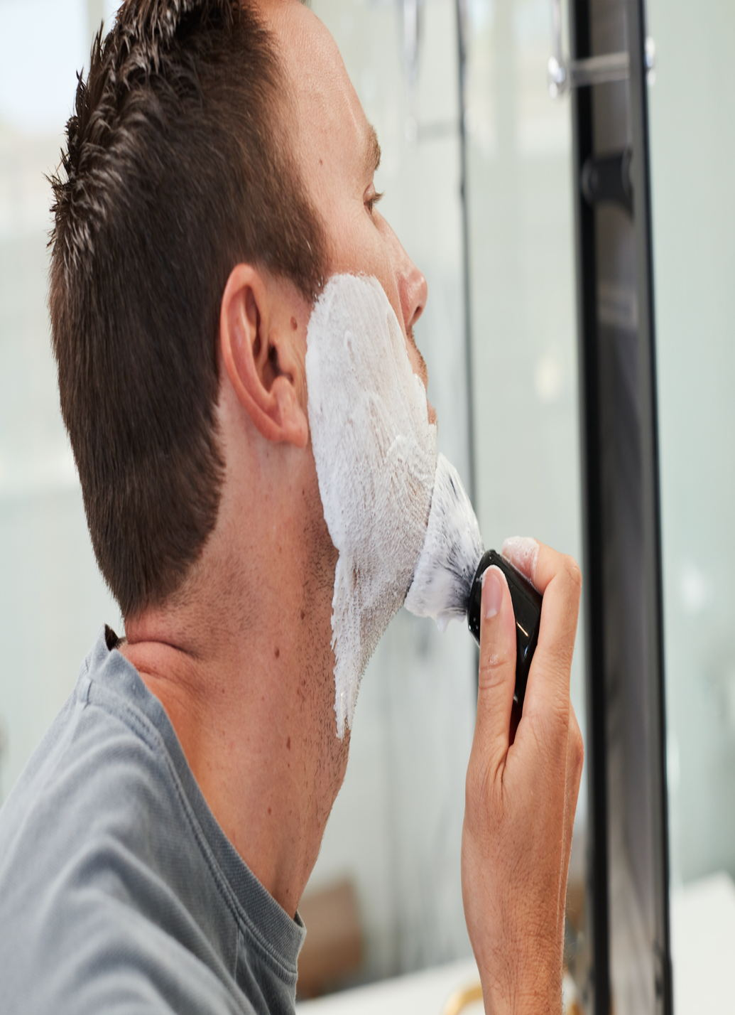 Man with shaving cream on his face applying shaving cream with a shave brush to his chin
