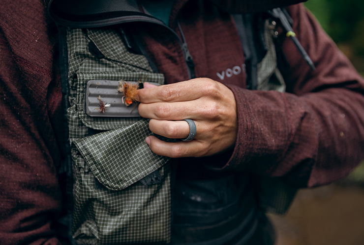 Man wearing a groove ring while holding a fly fishing fly and wearing a fishing vest