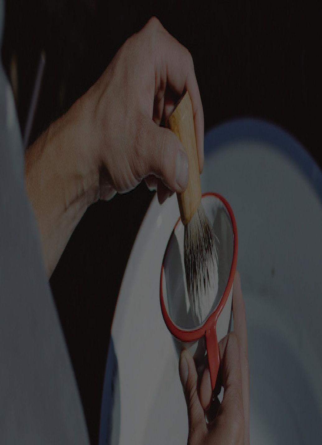 A hand dipping a shaving brush into shaving cream