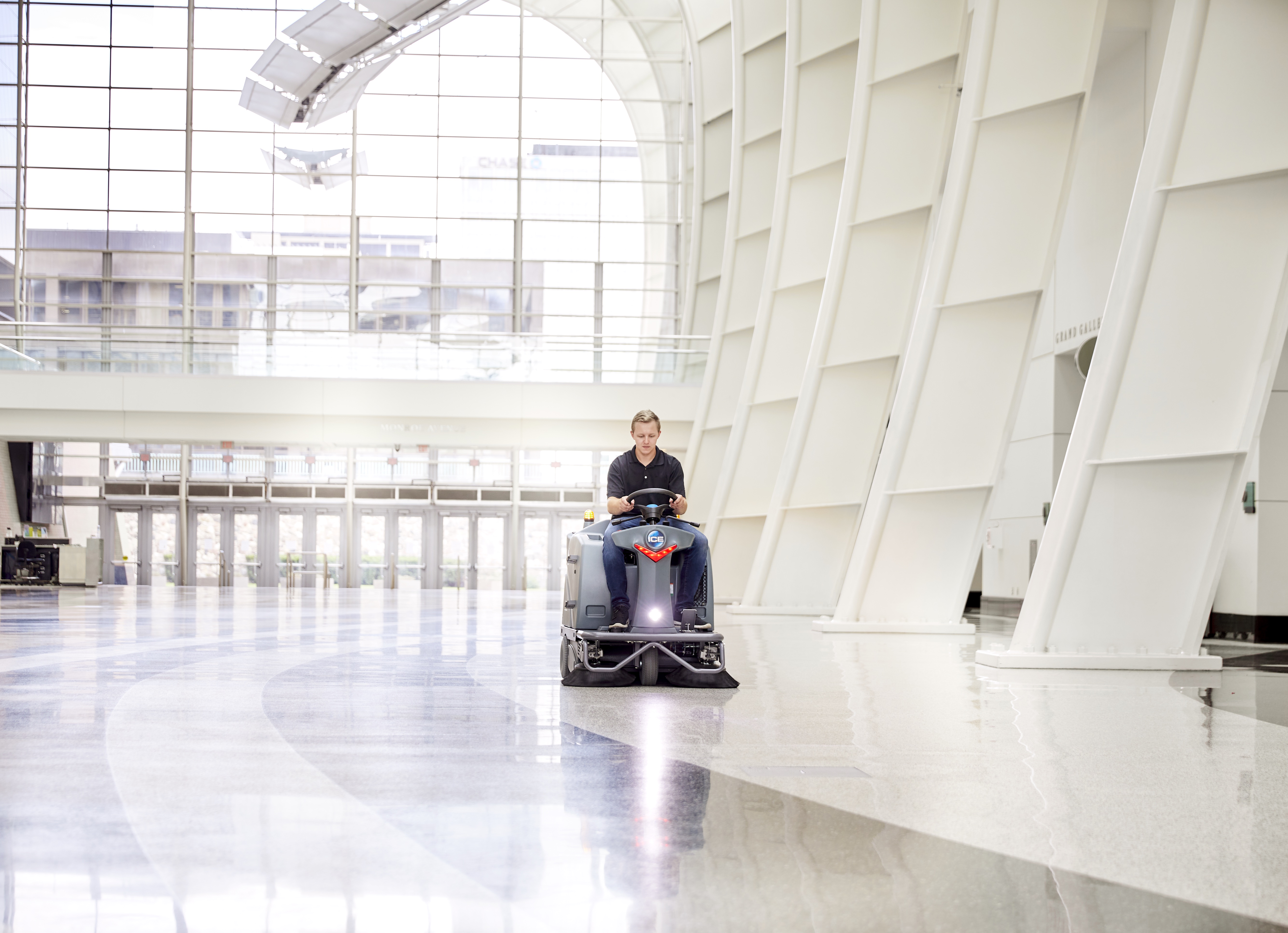 Machine operator riding the is1100L sweeper in a convention center
