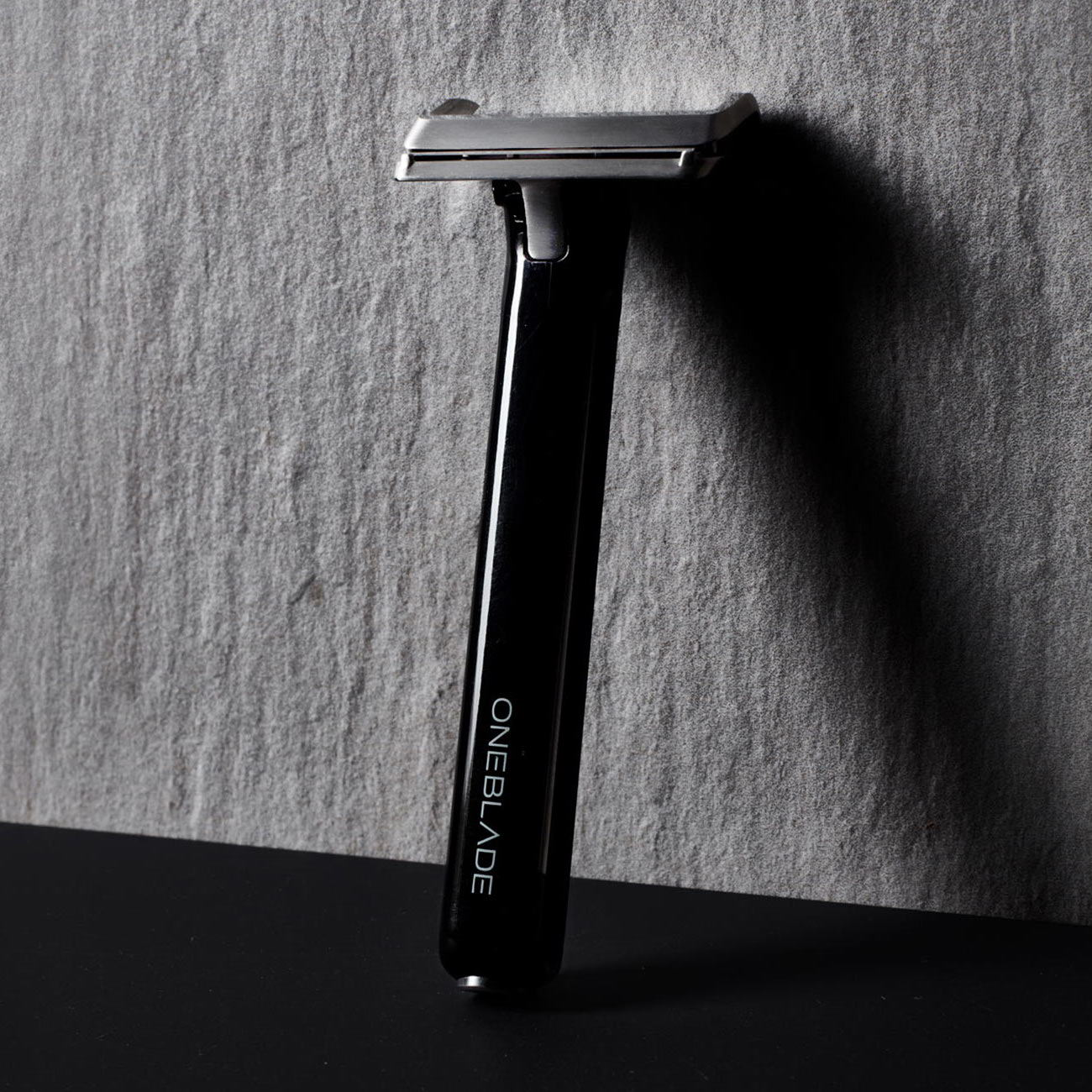OneBlade razor laying against a wall