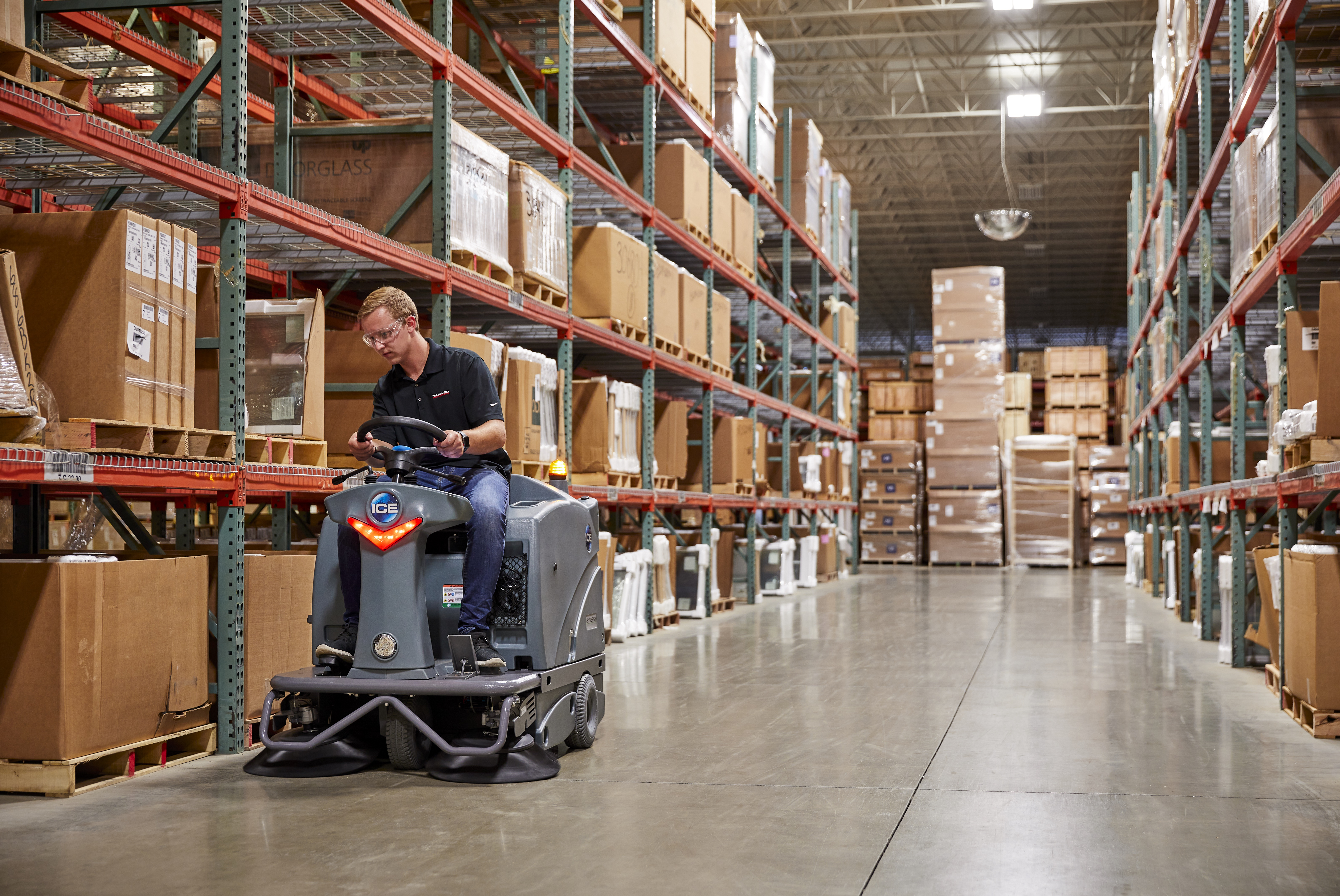 Machine operator riding the is1100L sweeper in a warehouse