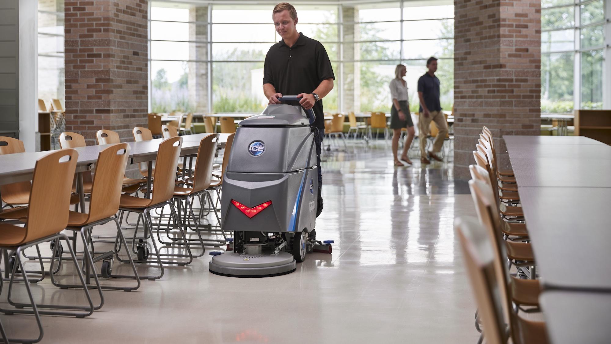 Machine operator pushing the i20btl scrubber through school cafeteria