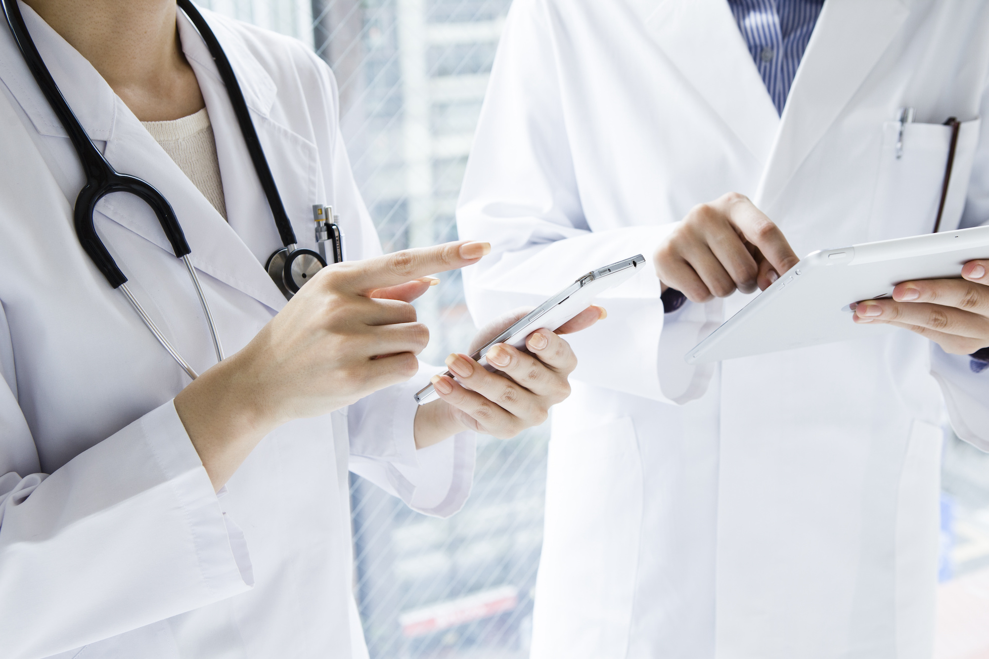 Doctors reviewing data on iphone and ipad at hospital