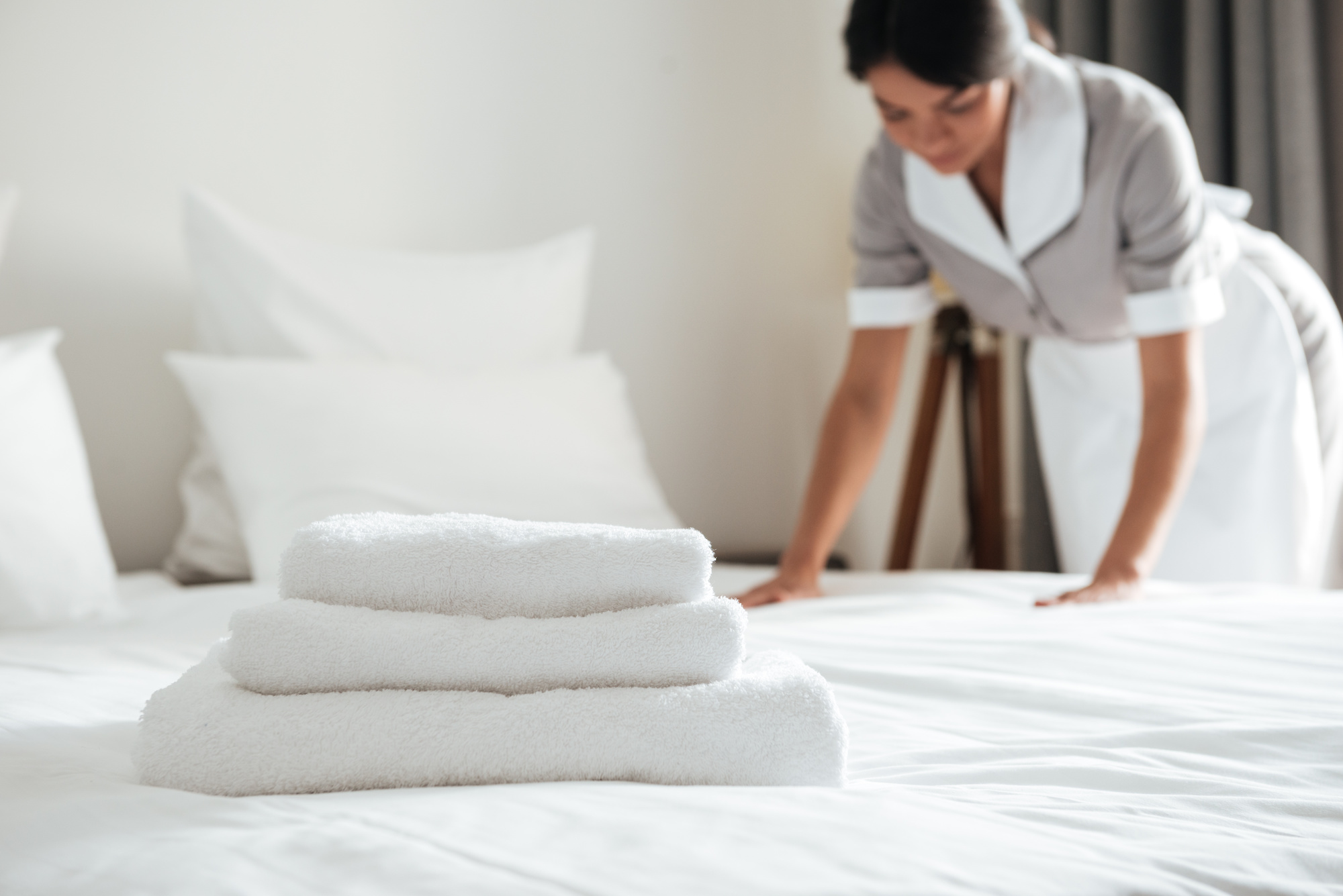 Housekeeping making a bed in a hotel